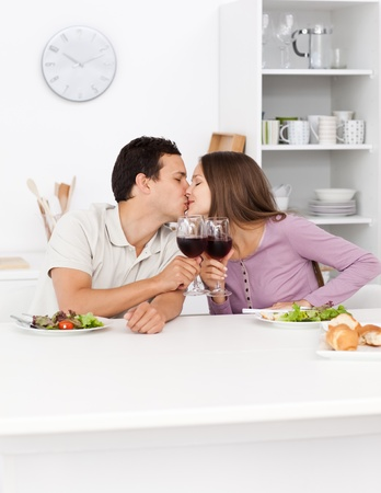 Young couple kissing with red wine in their hands during lunch  photo