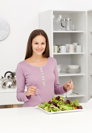 Cute woman mixing a salad standing in the kitchen photo