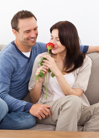 Cute woman smelling a red rose while relaxing on the sofa Stock Photo - 10197130