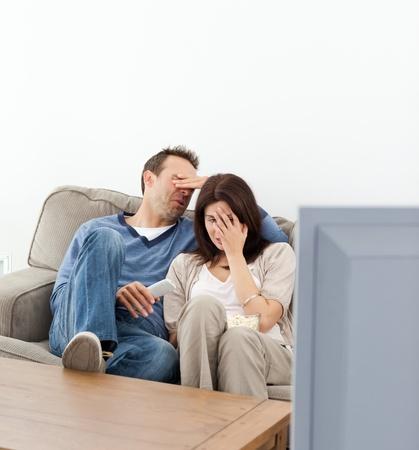pareja viendo tv: Pareja asustado ocultando sus rostros mientras ve�a una pel�cula de terror