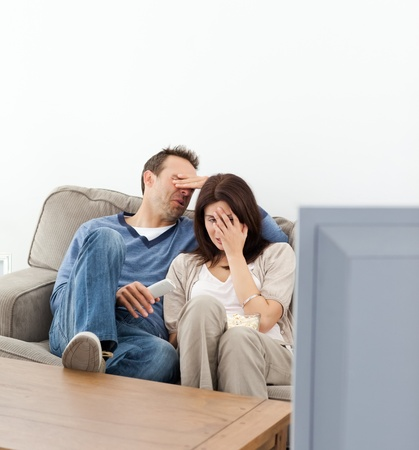 Scared couple hiding their faces while watching a horror movie photo