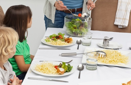 Mother serving salad to her children at lunch photo