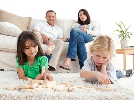 pareja en casa: Orgullosos padres buscan a sus hijos jugando con domin� en el piso Foto de archivo