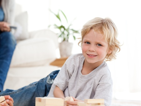 Cute child playing with dominoes in the living room photo