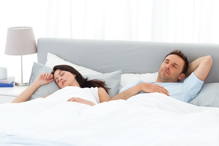 catnap: Serene couple sleeping on their bed in the morning Stock Photo