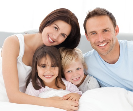 home comfort: Lovely family sitting together on the bed