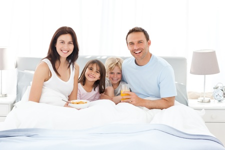 Happy family having breakfast together on the bed photo
