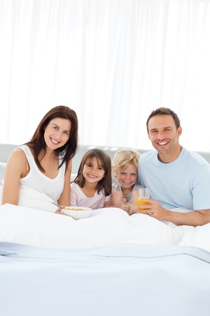 Happy brother and sister having breakfast with their parents on the bed  photo