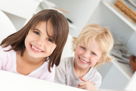 Happy children sitting at a table in the kitchen photo