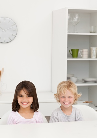 Little brother and sister smiling sitting at a table in the kitchen  photo