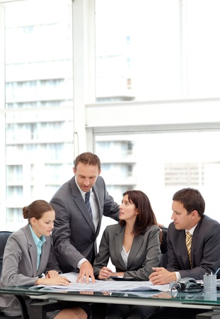 company employee: Successful manager showing a plan to his team during a meeting
