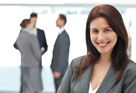 boss and employee: Happy businesswoman posing while her team discussing Stock Photo