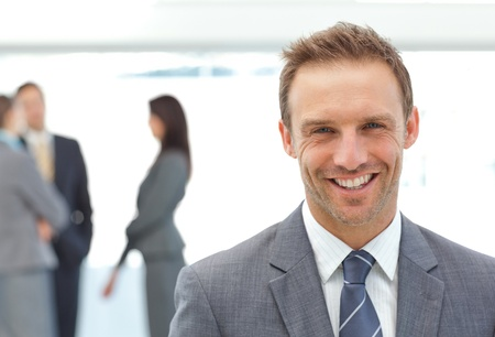 Happy businessman posing in front of his team photo