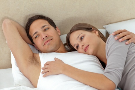 unbend: Pensive couple lying in each other