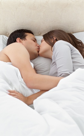 Adorable couple kissing while relaxing on the bed  photo