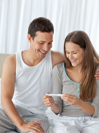 cravings: Happy couple looking at a pregnancy test on their bed