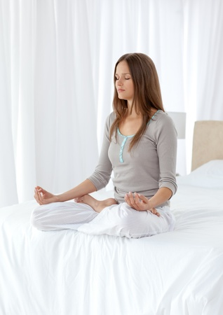 quietude: Quiet woman doing yoga exercises on the bed Imagens