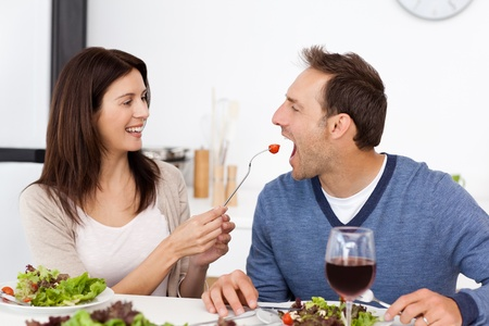 Pretty woman giving a tomato to her boyfriend while having lunch photo