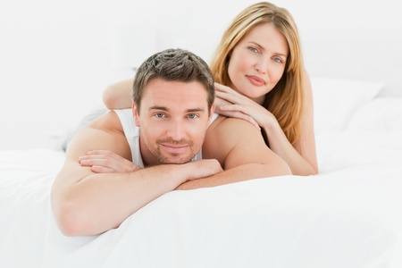 Lovely couple lying down together in their bed at home Stock Photo - 10196942