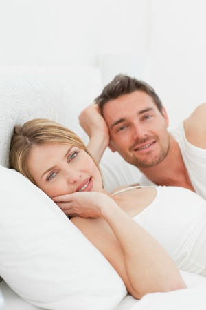 Cute couple lying down together in their bed photo