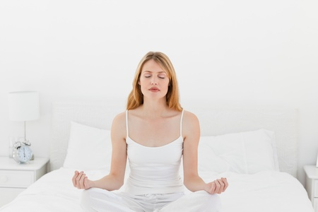 Woman practicing yoga on her bed Stock Photo - 10196734