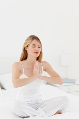 Woman practicing yoga on her bed photo