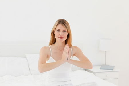 Woman practicing yoga on her bed Stock Photo - 10196772