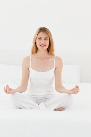Woman practicing yoga on her bed Stock Photo - 10195732