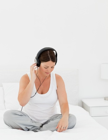 Woman listening to music on her bed photo