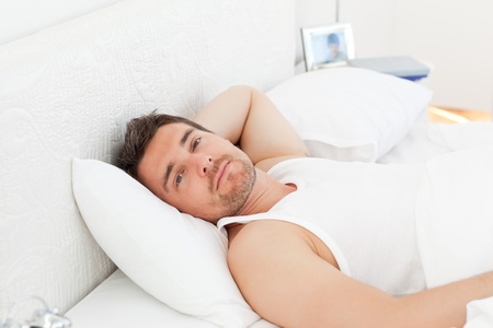 A relaxed man in his bed before waking up photo