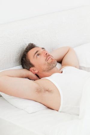 despertarse: Un hombre tranquilo en su cama antes de despertar