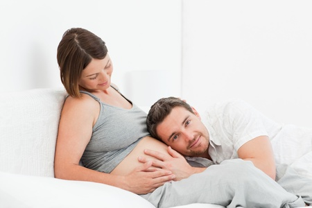 pregnant couple: Husband listening to his wife