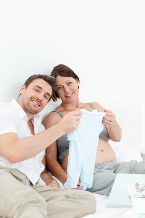 Young futur parents with chlidrens clothes photo