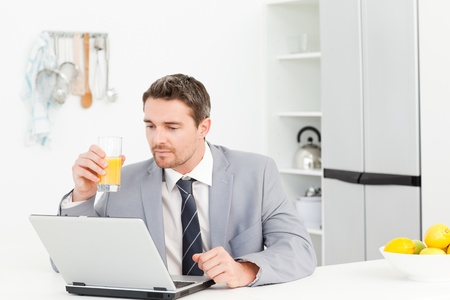 Businessman drinking while he is looking at his laptop photo