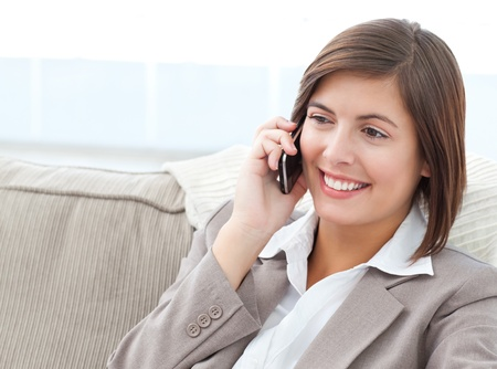 Smilng Businesswoman phoning on her sofa  photo