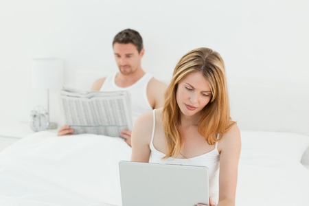 Woman looking at  laptop while her husband is reading a newspaper  photo
