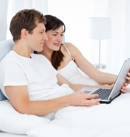 Young couple watching videos on their computer at home photo