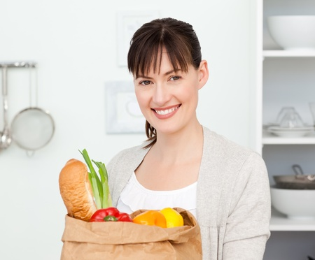 Woman with shoping bags in the kitchen  photo