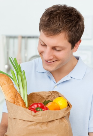 Man with shoping bags in the kitchen  photo