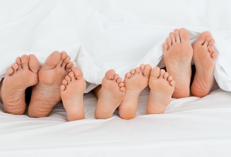 man feet:  Family on the bed  at home with their feet showing