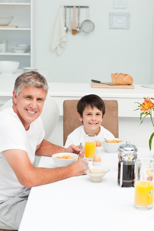 Father having his breakfast with his son photo