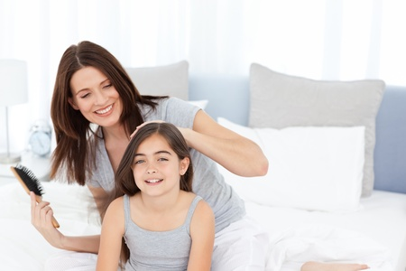 mother       care: Woman brushing her daughter Stock Photo