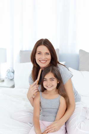 comb: Woman brushing her daughter Stock Photo