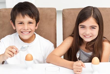 eating breakfast: Children having breakfast in the kitchen