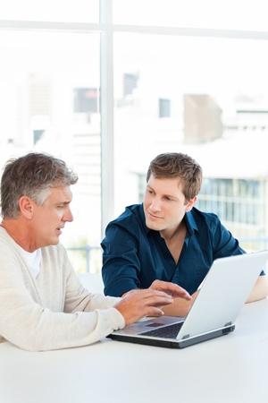 Two businessman working on their laptop photo