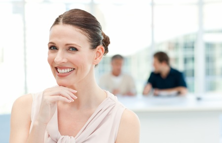 Smiling businesswoman looking at the camera while her coworkers are talking photo