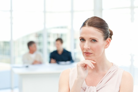 Serious businesswoman looking at the camera while her coworkers are talking photo