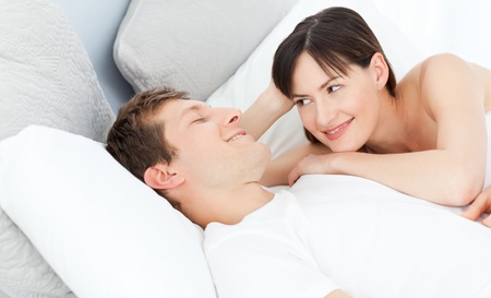 Happy couple lying down together on their bed photo
