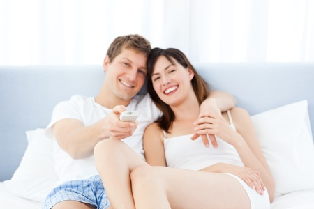 Smiling couple watching tv at home photo