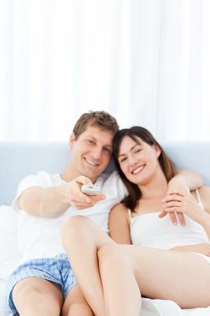 pareja viendo tv: Sonriente pareja viendo televisi�n en su casa